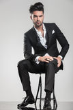 Stiligt sammanträde för ung man på en stol arkivfoton