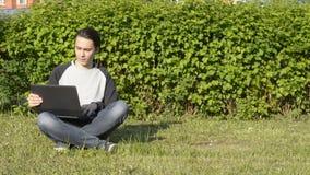 Stiligt sammanträde för ung man på gräset i parkera och att arbeta med bärbara datorn stock video