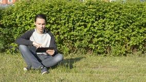 Stiligt sammanträde för ung man på gräset i parkera och att arbeta med ipad stock video