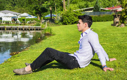 Stiligt sammanträde för ung man på gräsmattanexto till en sjö royaltyfri bild