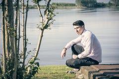 Stiligt sammanträde för ung man på gräsmattanexto till en sjö royaltyfri fotografi