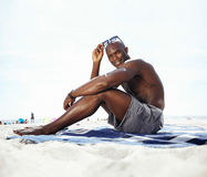 Stiligt sammanträde för ung man på stranden royaltyfria bilder