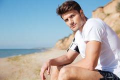 Stiligt sammanträde för ung man på stranden arkivbild