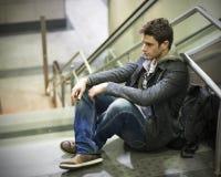 Stiligt sammanträde för ung man på trappa royaltyfri foto