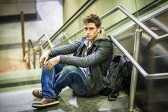 Stiligt sammanträde för ung man på trappa royaltyfri fotografi