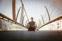 Stiligt sammanträde för ung man utomhus i stads- miljö royaltyfri bild
