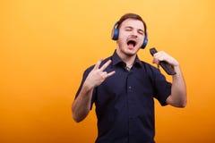 Stiligt sjunga för ung man vaggar musik med hans hörlurar över gul bakgrund arkivfoton