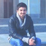 Stiligt studentsammanträde för ung man på momenten av högskolan royaltyfria foton