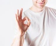Stiligt symbol för godkännande för grabbhipstervisning i vitt le för skjorta, royaltyfri fotografi