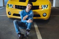 Stiligt tillfälligt mansammanträde nära den moderna gula sportbilen Mode modernt annonsering Arkivbilder