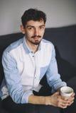 Stiligt tillfälligt mansammanträde på soffan som har kaffe fotografering för bildbyråer