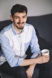 Stiligt tillfälligt mansammanträde på soffan som har kaffe royaltyfri foto