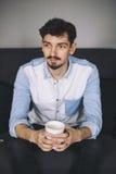 Stiligt tillfälligt mansammanträde på soffan som har kaffe arkivfoto
