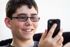 Stiligt tonårigt genom att använda hans smartphone arkivfoton