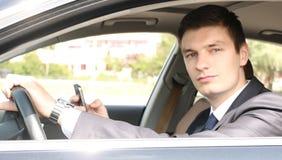 Stiligt ungt affärsmansammanträde i hans bil Royaltyfri Bild