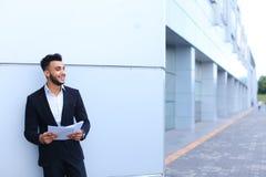 Stiligt ungt arabiskt grabbaffärsmanle och blickar bort med arkivbilder