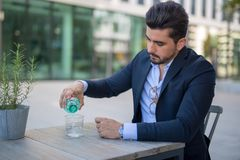 Stiligt ungt hällande vatten för affärsman från en flaska in i hans exponeringsglas arkivfoto