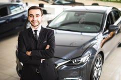 Stiligt ungt klassiskt bilförsäljareanseende på återförsäljaren royaltyfri fotografi