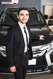Stiligt ungt klassiskt bilförsäljareanseende på återförsäljaren framme av den nya bilen fotografering för bildbyråer