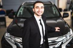 Stiligt ungt klassiskt bilförsäljareanseende på återförsäljaren framme av den nya bilen royaltyfria foton