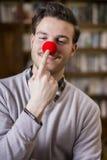 Stiligt ungt le för man och rörande röd clownnäsa arkivbild