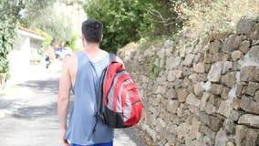 Stiligt utomhus- fotvandra för ung man på den lantliga vägen lager videofilmer