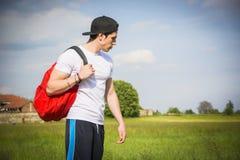 Stiligt utomhus- fotvandra för ung man på den lantliga vägen arkivfoton