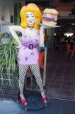 Stiliserad servitris som tjänar som en hamburgare utanför ett kafé Fotografering för Bildbyråer