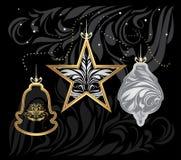 Stiliserade guld- och silverjulleksaker på dekorativ svart bakgrund Arkivbild