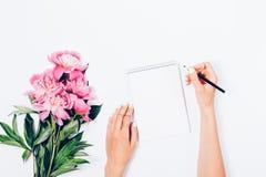 Stiliserat kvinnligt skrivbord med buketten av nytt ljus - rosa pioner royaltyfri foto