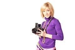 Stilish girl holding retro camera. Portrait of a stilish girl clicking camera smiling Stock Images