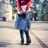 Stilish woman with fashion bag and boots standing on street Royalty Free Stock Image