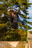 Stilish young man with a long beard and with a long hair who is. Jumping from the bridge  sunny day on summer Stock Photography