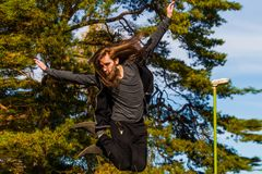 Stilish young man with a long beard and with a long hair who is. Jumping from the bridge  sunny day on summer Royalty Free Stock Photos