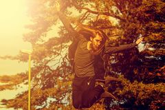 Stilish young man with a long beard and with a long hair who is. Jumping from the bridge  sunny day on summer. Vintage tone Stock Images