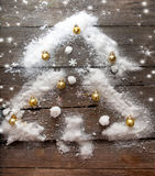 Stilisierter Design Weihnachtsbaum mit Weihnachtsbällen und Schnee auf hölzernem Hintergrund Lizenzfreies Stockfoto