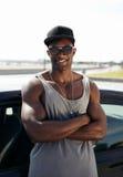 Stilisierter junger muskulöser Mann, der am Auto sich lehnt Stockfotos