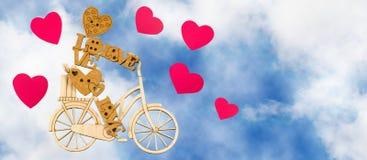 stilisierter Spielzeugmann auf einem Fahrrad und dekorative Herzen auf Himmelhintergrund Lizenzfreies Stockfoto