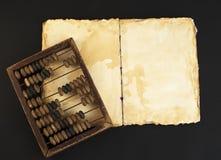 Stilisiertes altes Buch mit Abakus des erfahrenen Arbeiters Stockfotos