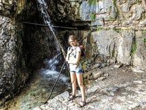 Stilisiertes Bild des reisenden Mädchens nahe dem Wasserfall stockfoto