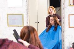 Stilist, der Haar der Brunette-Frau im Salon anredet Lizenzfreie Stockbilder