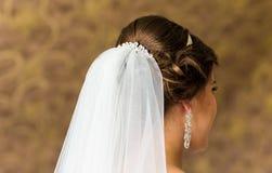 Stilist, der herauf die Frisur und den Brautschleier einer Braut vor der Hochzeit feststeckt lizenzfreies stockbild