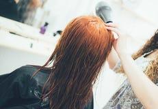Stilist die in de schoonheidssalon, het kapsel en haar het stileren werken royalty-vrije stock foto