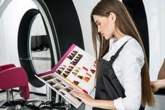 Stilist die de steekproeven van de haarkleur bekijken royalty-vrije stock foto