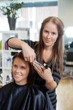 Stilist die een Kapsel geven aan Vrouw royalty-vrije stock fotografie