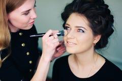 Stilist die in een schoonheidssalon en een aardige dame werken royalty-vrije stock foto's