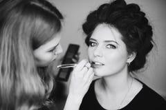 Stilist die in een schoonheidssalon en een aardige dame werken royalty-vrije stock afbeelding