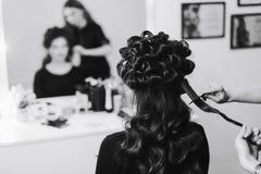 Stilist die in een schoonheidssalon en een aardige dame werken royalty-vrije stock afbeeldingen