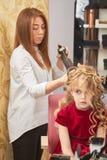 Stilist die hairspray, meisje gebruiken stock foto's
