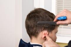 Stilist die het haar van een jongen nat maken om een kapsel te maken royalty-vrije stock afbeeldingen